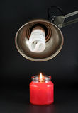 Energy saving bulb and candle. Energy saving bulb and lit up red candle on black background Royalty Free Stock Photos