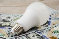 Energy saving bulb on dollars stock photos