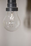 Energy saving bulb in dusty environment with shadow on the wall Royalty Free Stock Photography