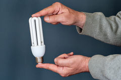 Energy saving bulb in hands Royalty Free Stock Photo