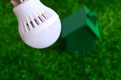 Energy saving, bulb light and a green house on the lawn. Stock Photo