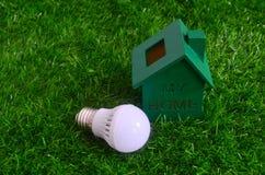 Energy saving, bulb light and a green house on the lawn. Stock Photos