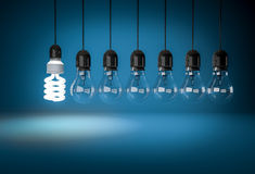 Energy saving bulb lighting incandescent bulbs on wires over blu Stock Images