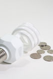 Energy Saving bulb and spare change Royalty Free Stock Photography
