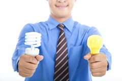 Energy saving  bulb and tradition bulb. Smiling businessman holding energy saving light bulb and tradition light bulb Stock Photo