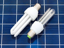 Energy saving bulbs. LED and CFL bulbs set on a solar panel Royalty Free Stock Photo