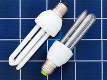 Energy saving bulbs. LED and CFL bulbs set on a solar panel Royalty Free Stock Image