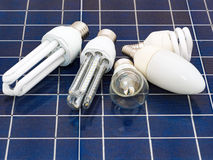 Energy saving bulbs. Various energy saving bulbs set on a solar panel Royalty Free Stock Photo