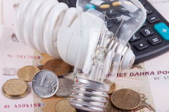 Energy saving concept. Electric light bulb, ruble money and calculator Royalty Free Stock Photo