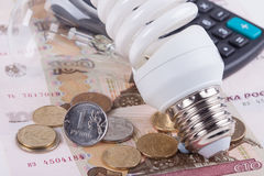 Energy saving concept. Electric light bulb, ruble money and calculator Stock Photos