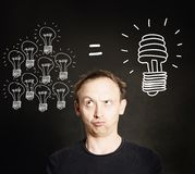 Energy Saving Concept. Man with Traditional. And Energy Efficient Light Bulbs on Blackboard Background royalty free stock image