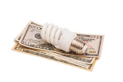 Energy Saving Concept represented by light bulb placed on dollar Stock Photo