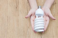 Energy saving concept, Woman hand holding light bulb on wooden background. Ideas light bulb in the hand stock photo
