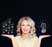 Energy saving concept. Woman with traditional. And energy efficient light bulbs. Orange old generation bulb and white energy saving bulb royalty free stock image
