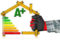 Energy Saving Concept - Wooden Meter. Hand with work glove holding a yellow wooden meter ruler in the shape of house with energy efficiency rating. Isolated on stock illustration