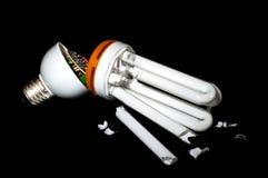 Energy saving lamp. Broken energy saving lamp on a black background. problem utilization Stock Images