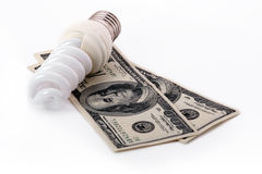 Energy saving lamp. Isolated with two 100 dollar notes on white Stock Photo