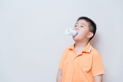 Energy saving lamp in Asian boy mouth. Concept idea, on grey wall background with soft shadow Stock Photos