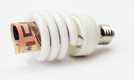 Energy saving lamp with banknote. Isolated on white background stock photos