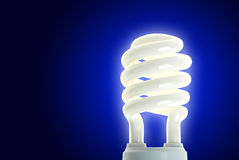 Energy Saving Lamp on Blue. Compact fluorescent energy saving environment friendly bulb on blue background royalty free stock images