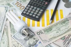 Energy saving lamp , chart and calculator on money background Energy saving,saving electricity concept. Energy saving lamp,chart and calculator on money Stock Image