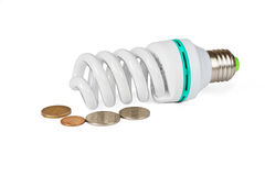 Energy saving lamp and coins Stock Image