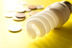 Energy saving lamp with coins on a yellow background. Close up. The concept of energy saving stock photography