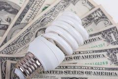 Energy saving lamp and dollars closeup Royalty Free Stock Photography