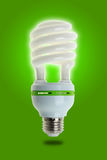 Energy Saving Lamp on Green. Compact fluorescent energy saving environment friendly bulb on green background royalty free stock photos