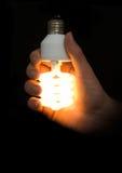 Energy-saving lamp in hand Stock Photos