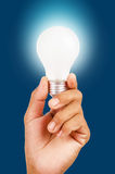 Energy saving lamp in hand. Energy saving lamp in hand on blue background stock photos