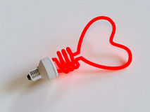 Energy saving lamp in the shape of the heart Royalty Free Stock Photography