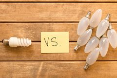 Energy-saving Lamp vs. incandescent lamp . The concept of energy. Saving . On a wooden table stock images