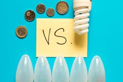 Energy-saving Lamp vs. incandescent lamp . The concept of energy. Saving . Isolated on turquoise background royalty free stock photos