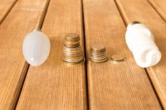 Energy-saving Lamp vs. incandescent lamp . The concept of energy. Saving . On a wooden table stock photos