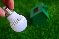 Energy saving, bulb light and a green house on the lawn. Stock Image