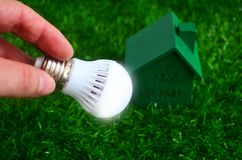 Energy saving, bulb light and a green house on the lawn. Royalty Free Stock Photography