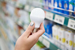 Energy saving LED lamp in hands of buyer at store Stock Image