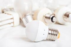 Energy saving LED lamp and several old light bulbs Stock Photography