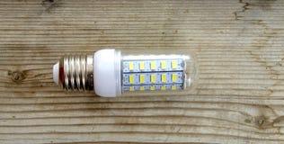 Energy saving LED light bulb on a wood background Stock Photo