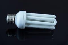 Energy saving light bulb. With reflection on black background Royalty Free Stock Photos