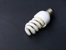 Energy saving light bulb. Saving light bulb on black background Stock Image