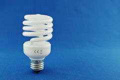 Energy Saving Light Bulb. Off centre energy saving light bulb on blue background Royalty Free Stock Image