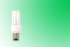 Energy saving light bulb. A lit up energy saving light bulb on a green background with copyspace Stock Photo
