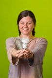 Energy saving light bulb. An environmentalist holds a compact fluorescent light bulb Royalty Free Stock Photography