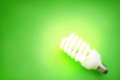 Energy saving light bulb. On green background Stock Photos
