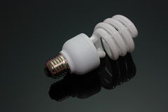 Energy saving light bulb on black background Stock Images