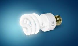 Energy saving light bulb. Close up of glowing energy saving light bulb on blue background Stock Photography