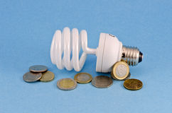 Energy saving light bulb and  coins on azure background Stock Photography