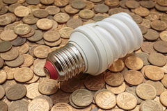 Energy saving light bulb on coins Stock Images